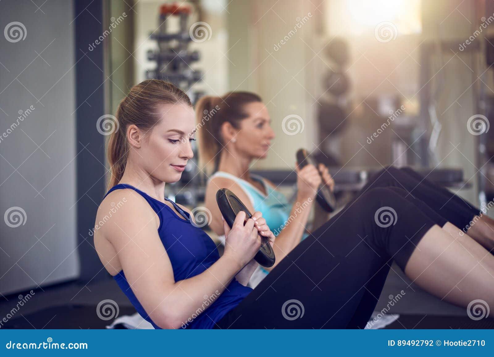 O par de mulheres adultas novas que fazem o músculo abdominal exercita