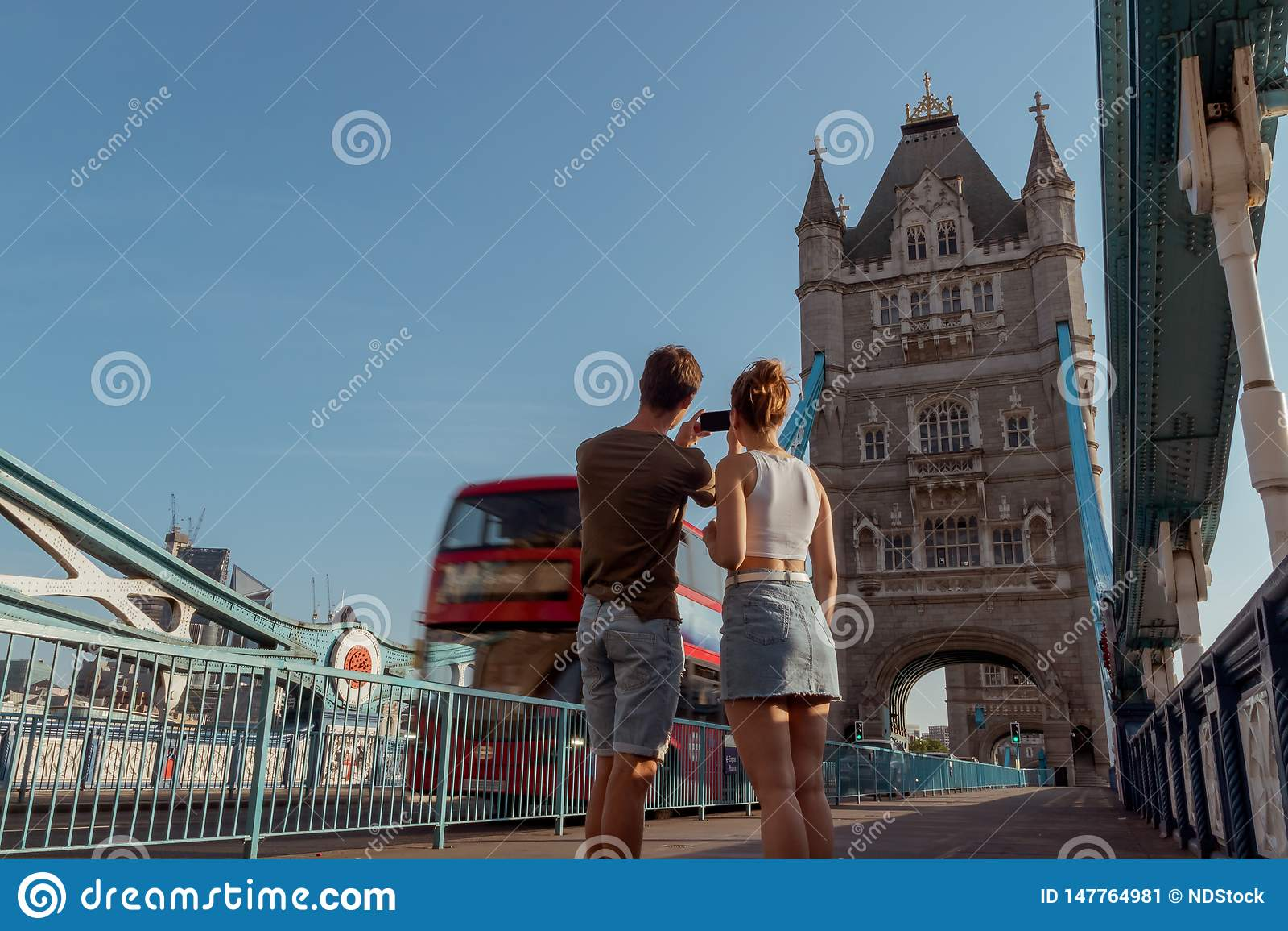 O par est? tomando uma imagem de um ?nibus vermelho do ?nibus de dois andares na ponte da torre em Londres