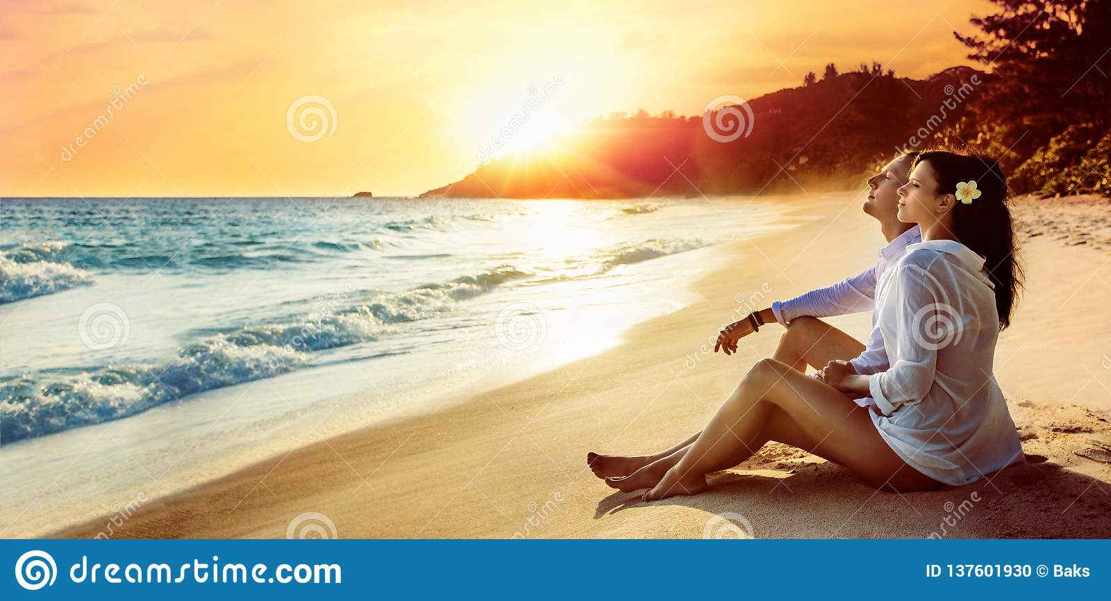 O par feliz senta-se na costa do oceano