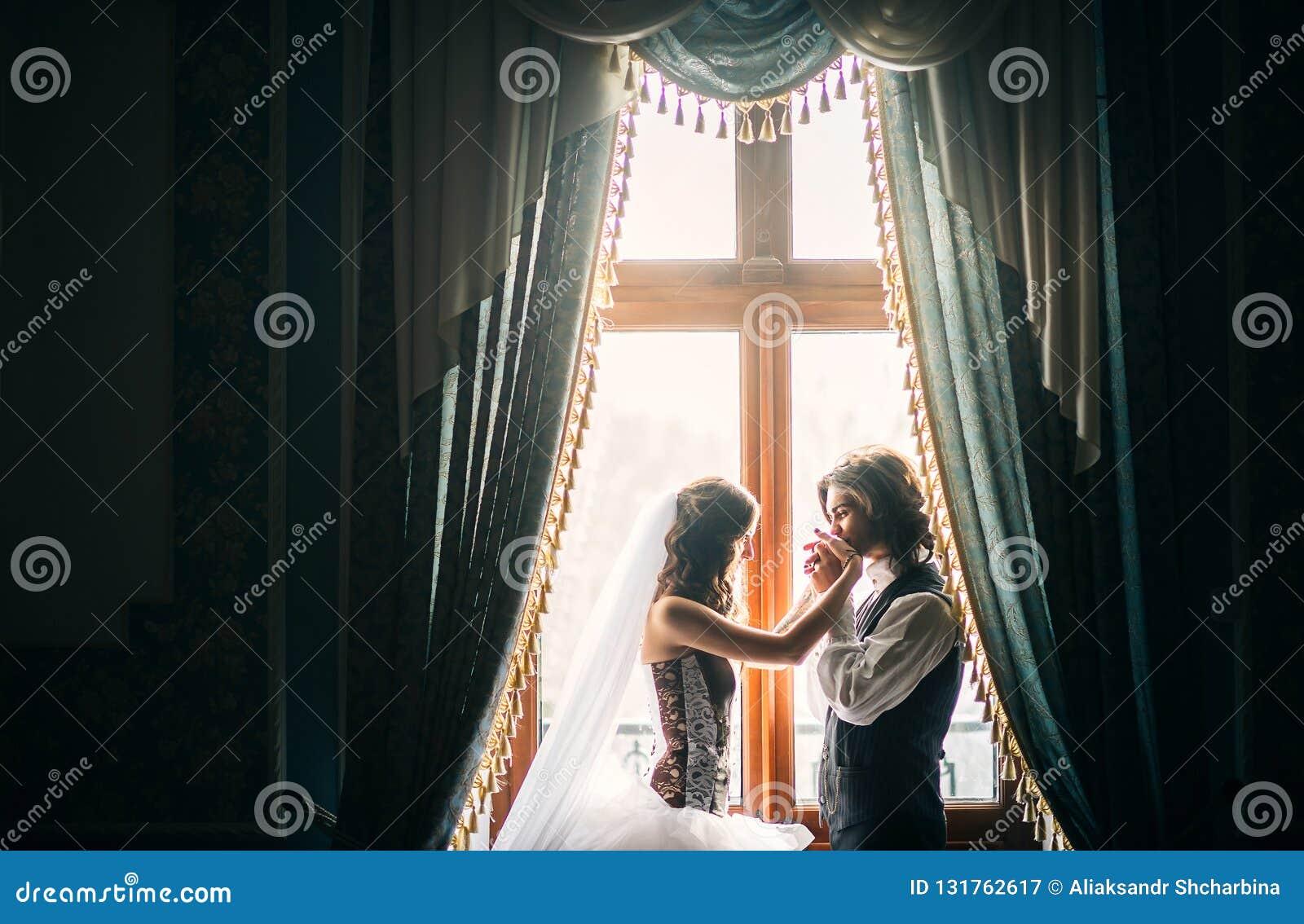 O par novo bonito, os custos perto de uma janela em um interior antigo, o noivo com ternura e o amor beijam o bride& x27; s
