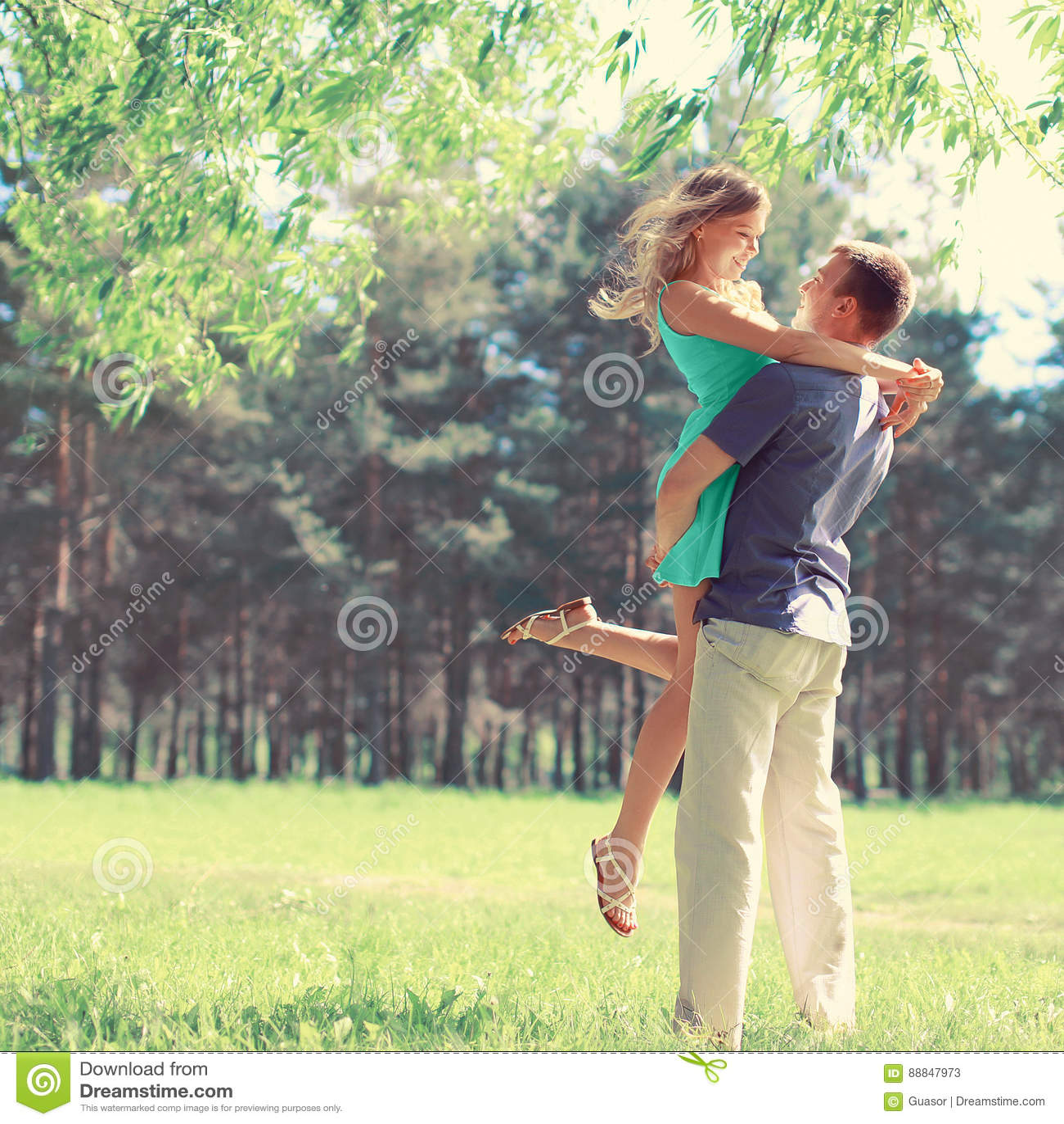 O par novo feliz no amor aprecia o dia de mola, homem loving que guarda sobre entrega a sua mulher o passeio despreocupado no par