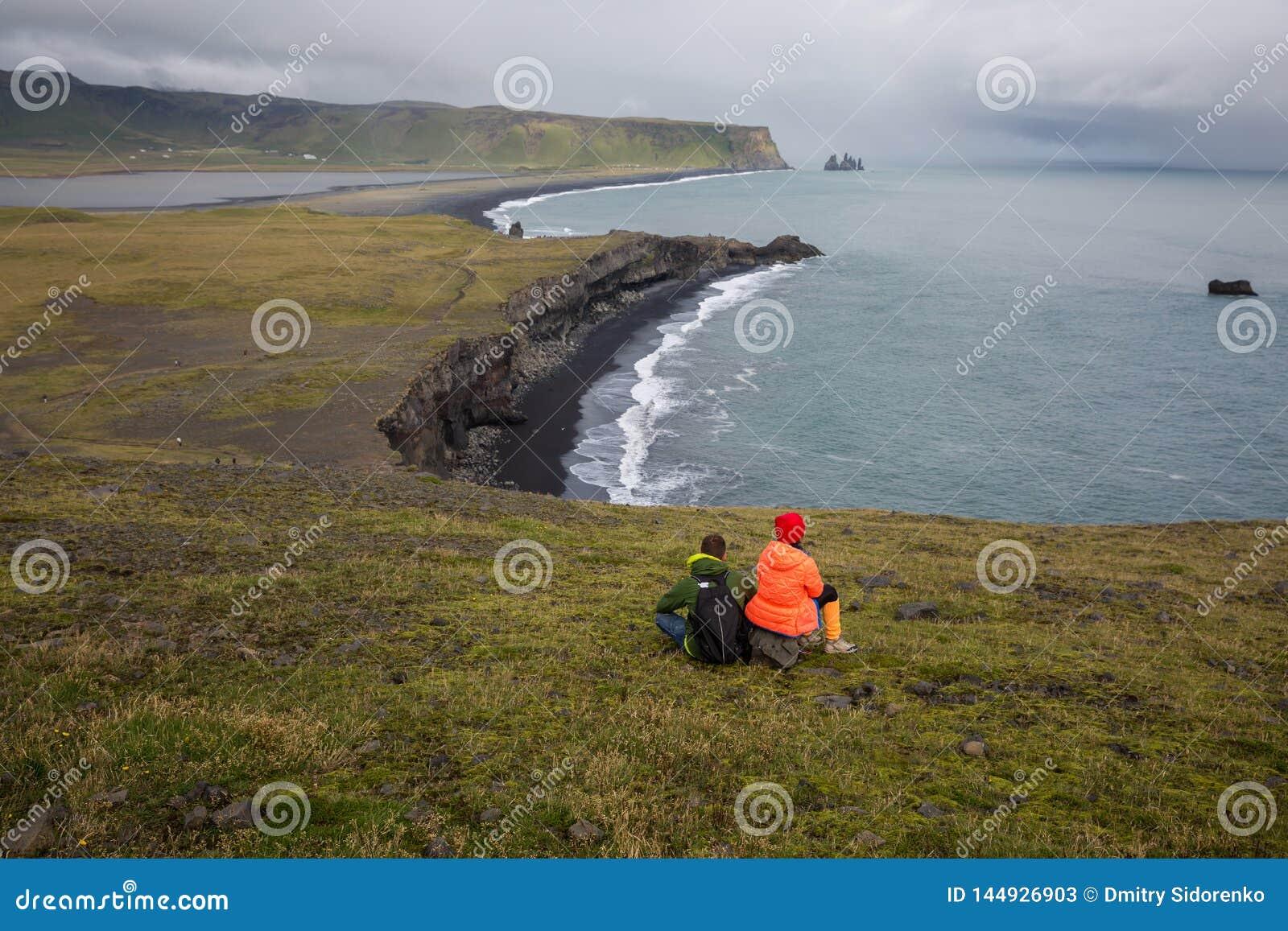 O par senta-se em um penhasco alto acima do mar e admira-se a baía