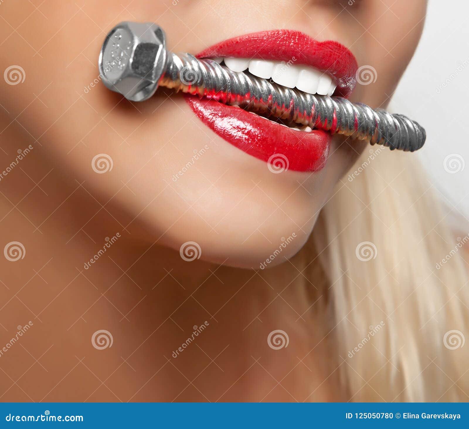 O parafuso de âncora grande nos dentes do ` s da menina com batom vermelho pintou os bordos