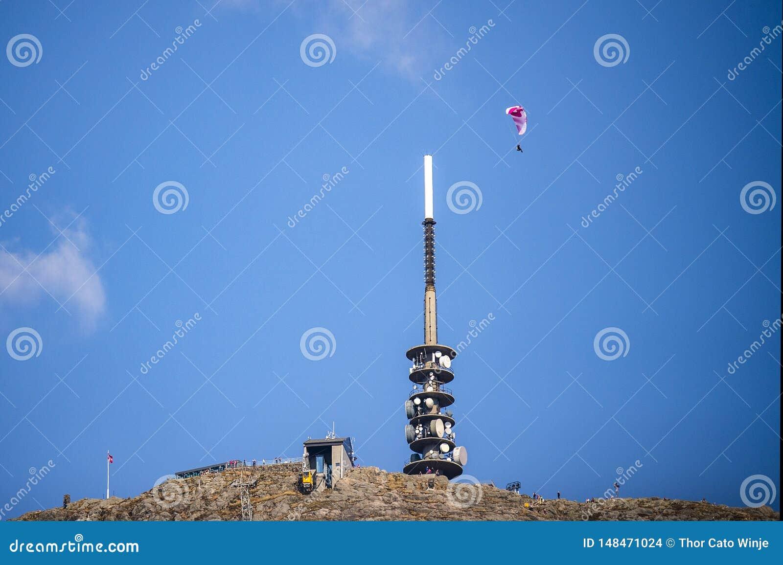 O parag-lider vermelho e branco contra um céu azul sobe sobre uma torre de antena e uma gôndola