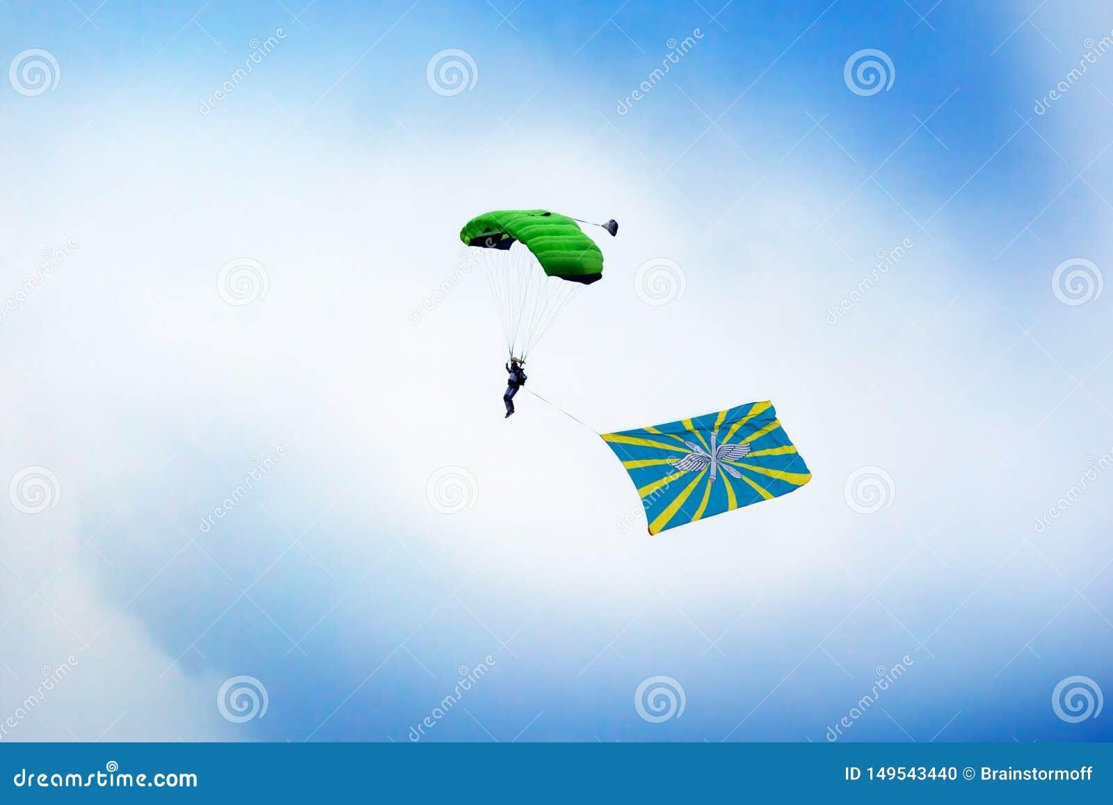 O paramilitar do russo salta com um paraquedas com a bandeira da força aérea do russo no céu azul claro e no fundo branco das nuv