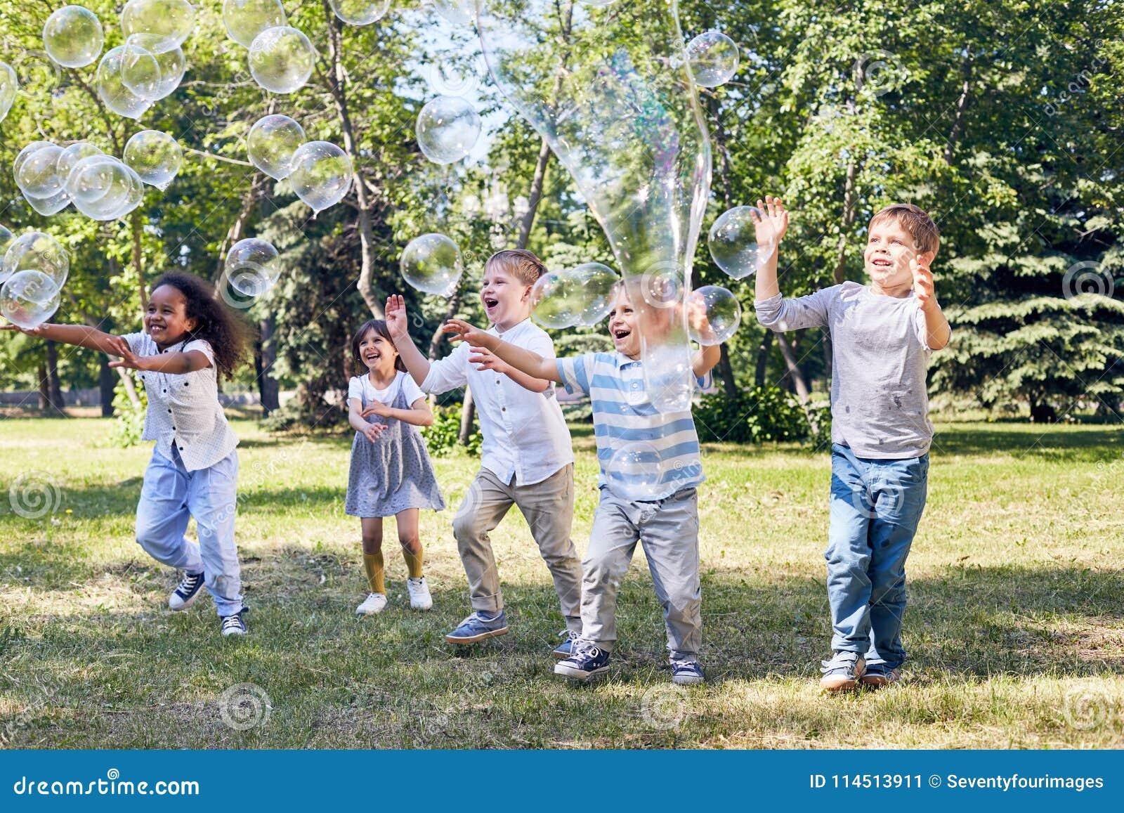 O partido das crianças no parque público verde