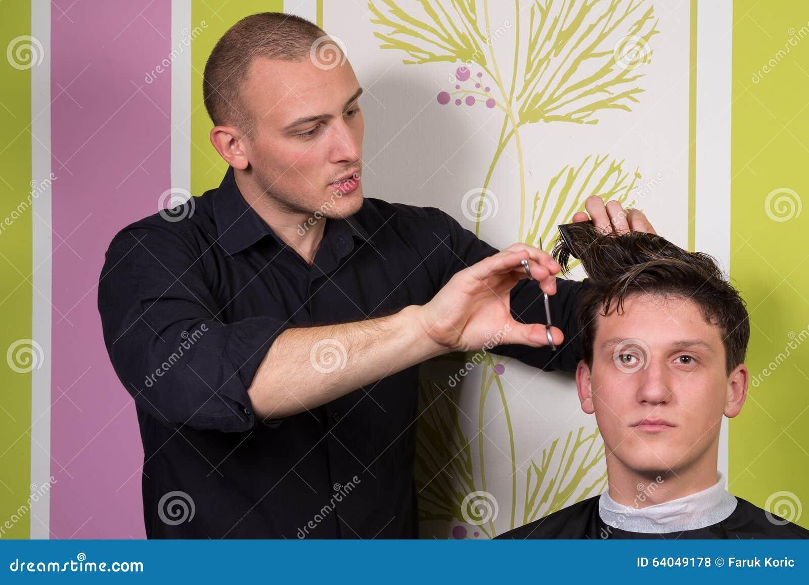 O penteado dos homens e haircutting com tosquiadeira de cabelo e scissor
