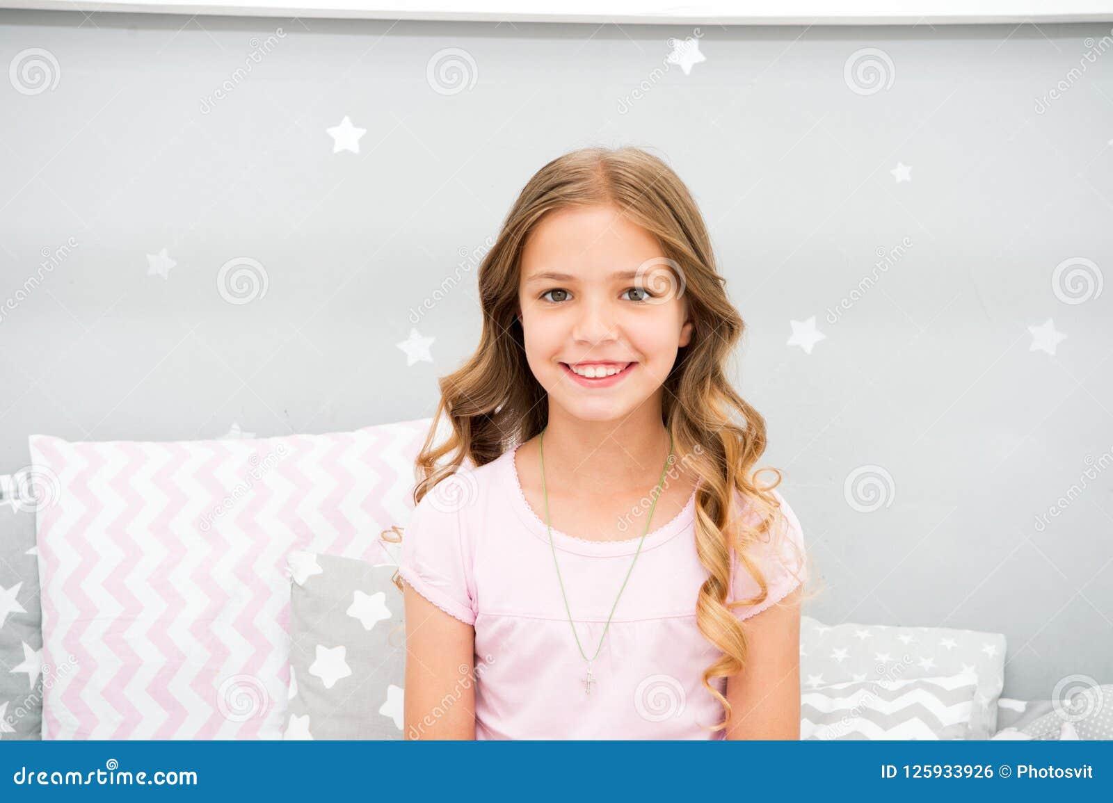 O penteado encaracolado perfeito da criança olha bonito Usa o condicionador ou a máscara com óleos orgânicos para manter o cabelo