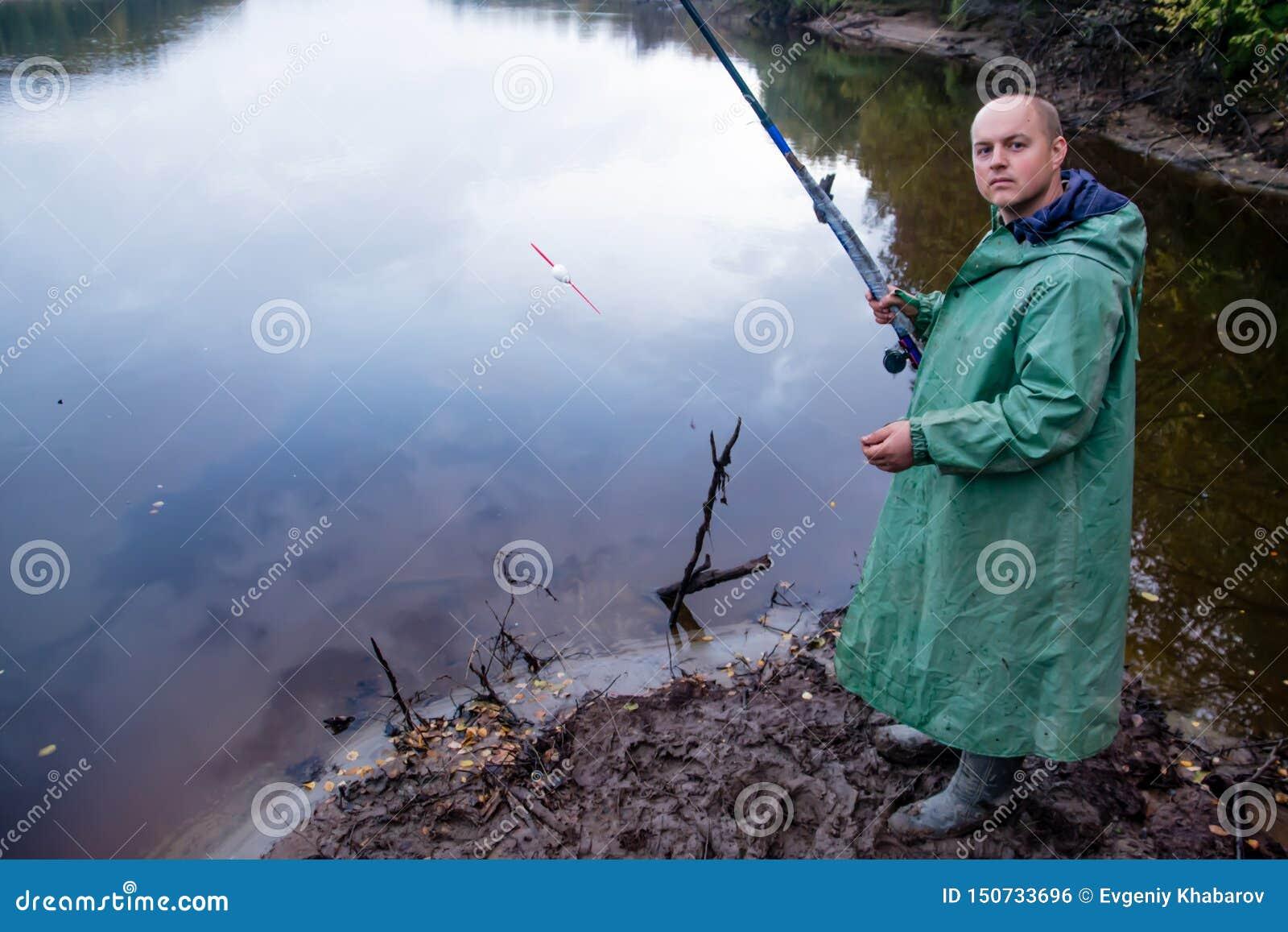 O pescador com vara de pesca pesca O canal do rio Nadym