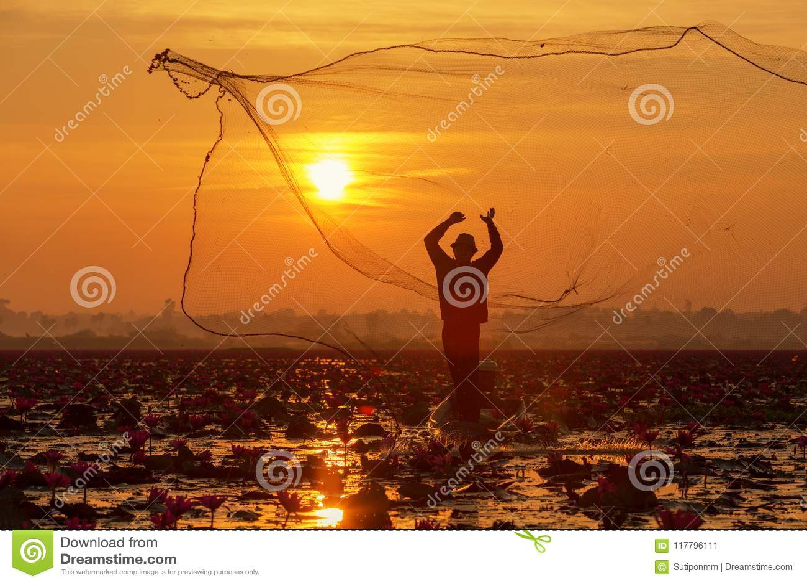 O pescador da silhueta que trabalha no barco no lago para o catchin