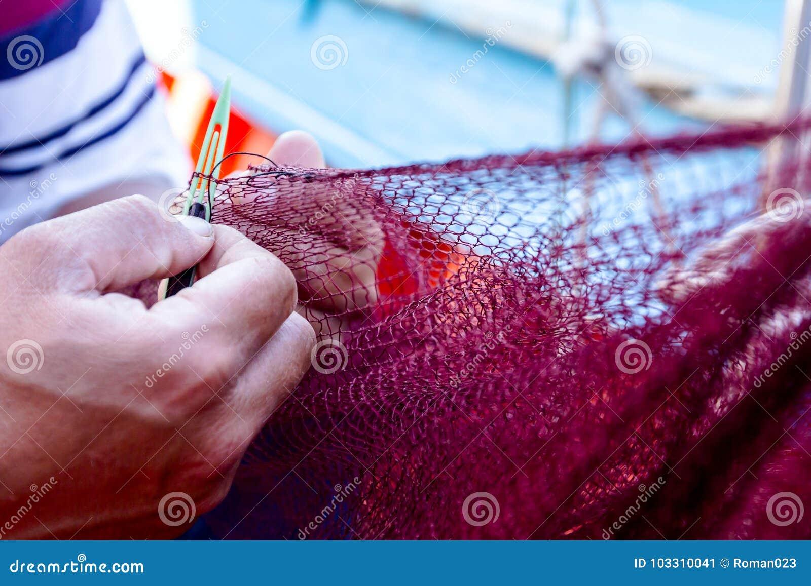 O pescador está fixando a rede dos peixes