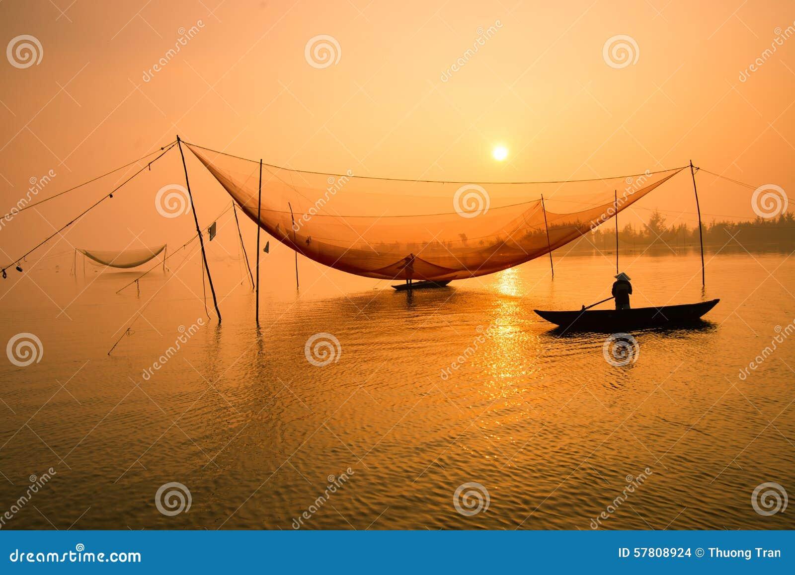 O pescador não identificado verifica suas redes no amanhecer no rio em Hoian, Vietname