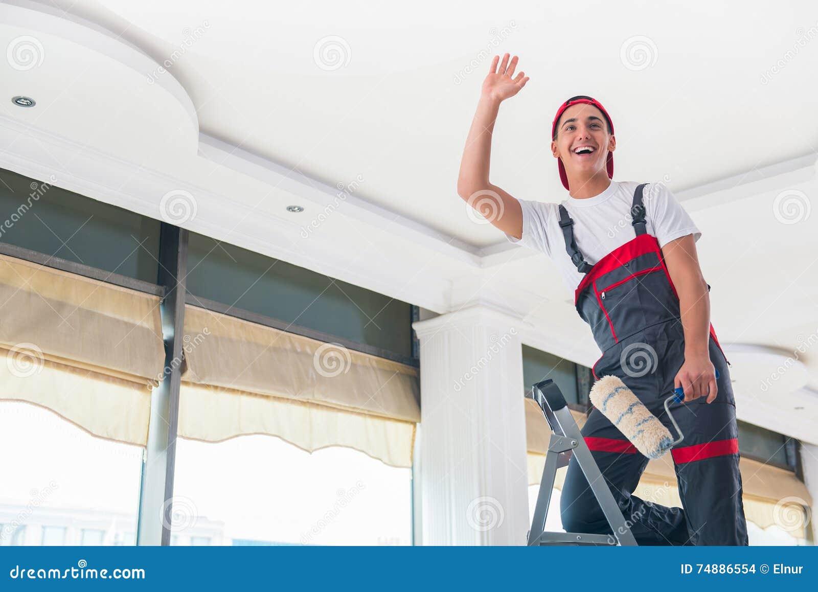 O pintor novo que pinta o teto no conceito da construção