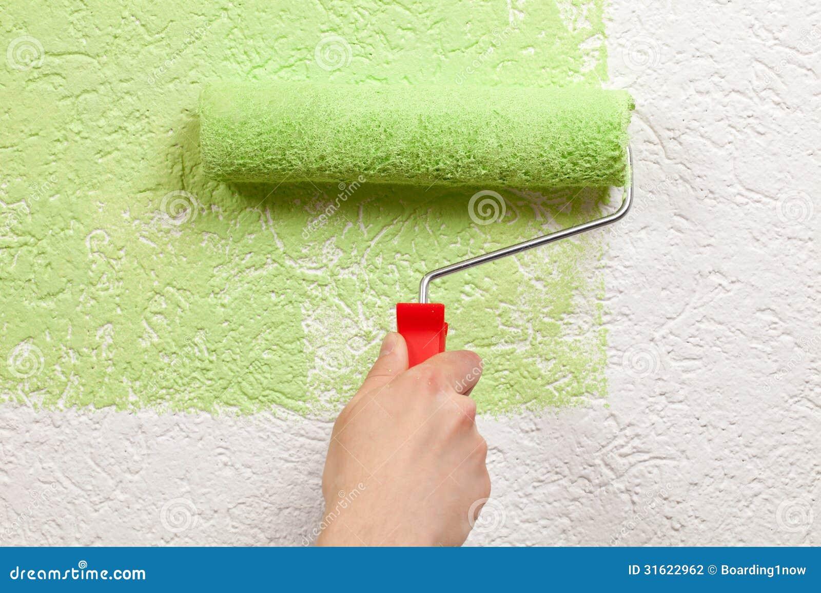 O pintor pinta uma parede com um rolo de pintura
