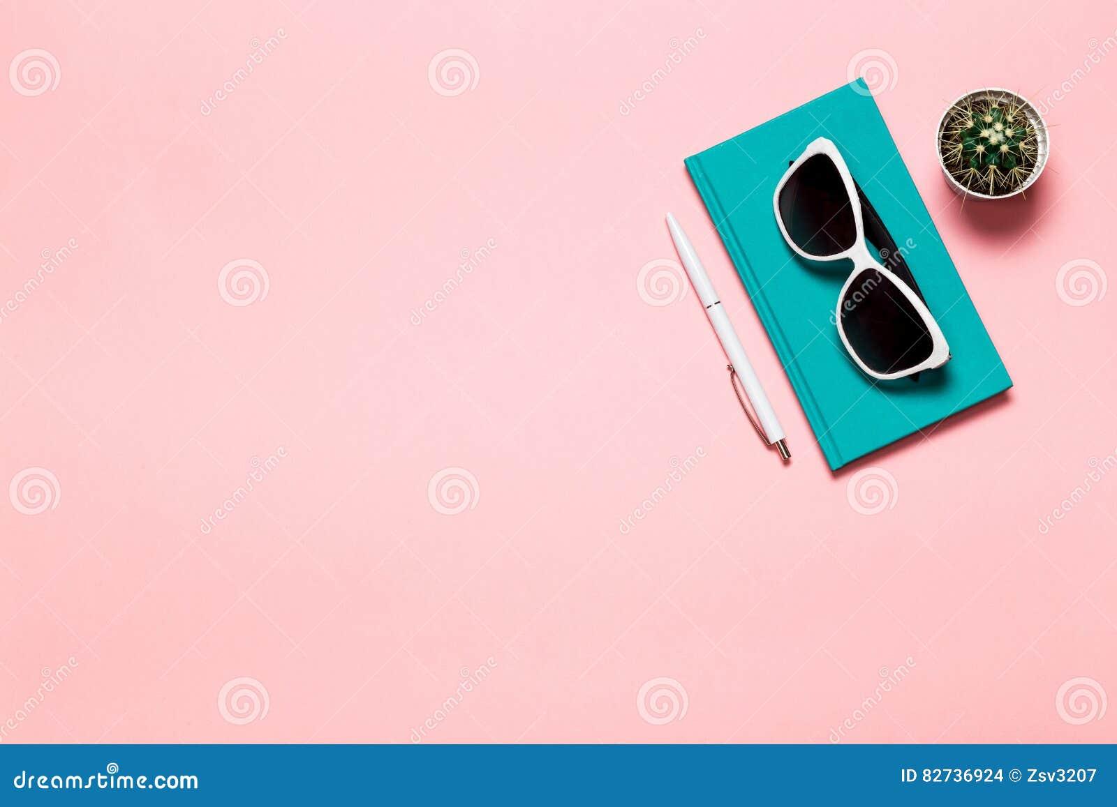O plano criativo coloca a foto da mesa do espaço de trabalho com caderno de água-marinha, monóculos, cacto com fundo do rosa do e
