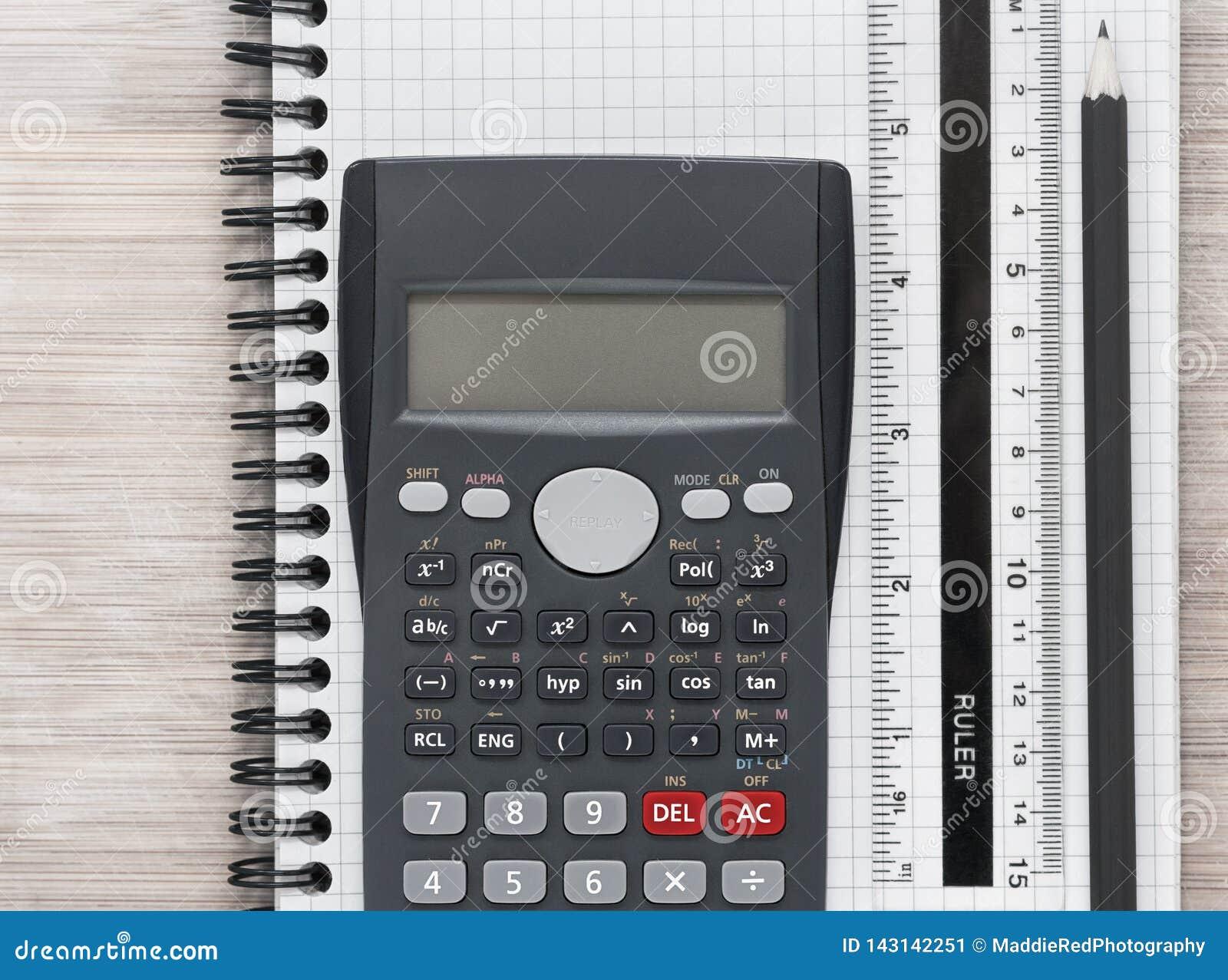 O plano da mesa coloca com calculadora, régua e lápis em um caderno