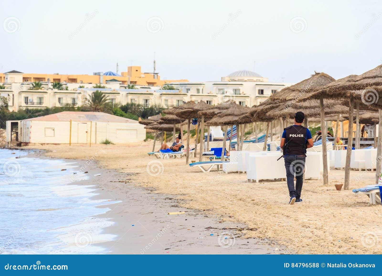 O polícia anda na praia