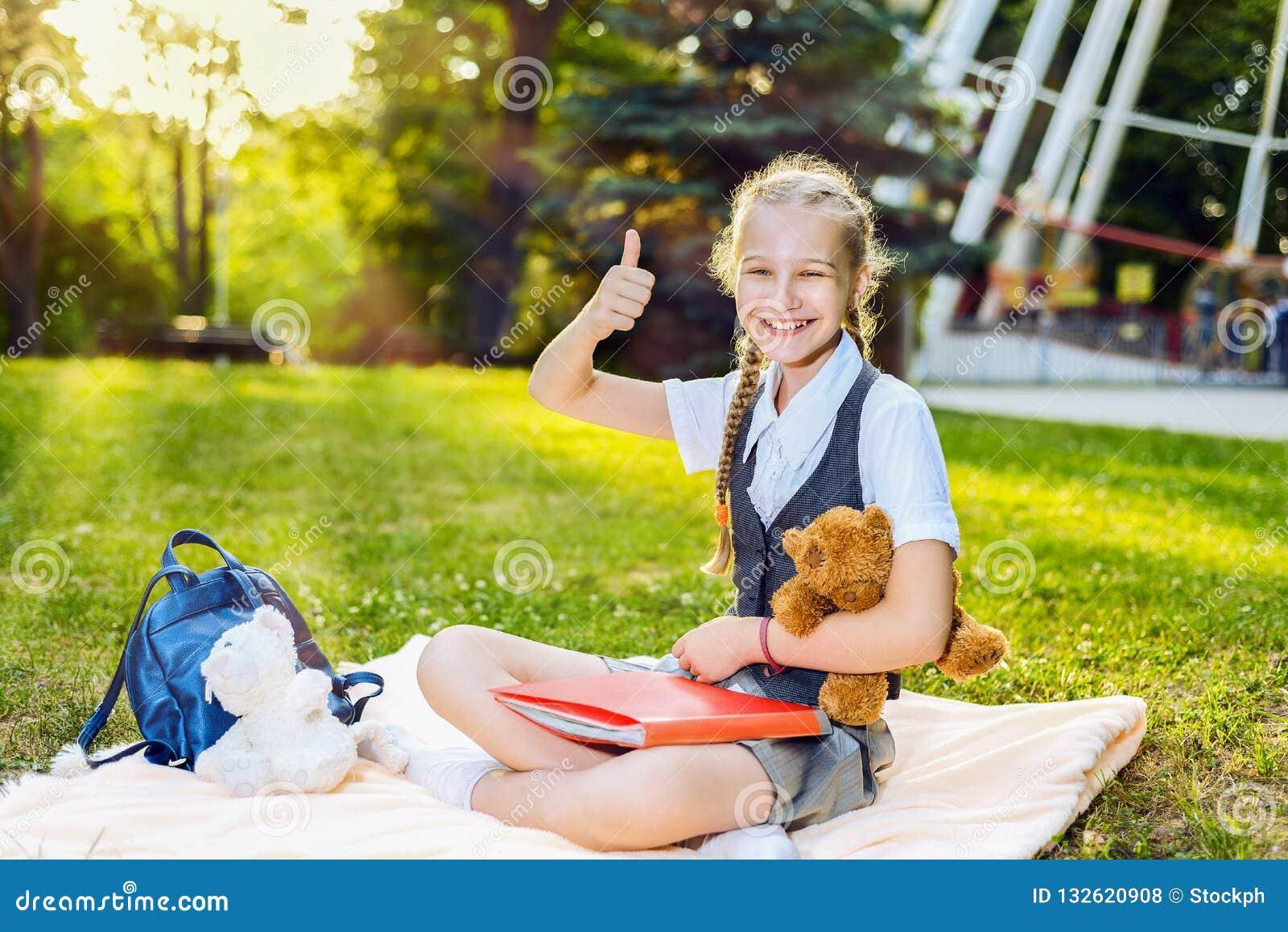O polegar mostrando de sorriso feliz do estudante da estudante senta-se acima em uma cobertura no parque em um dia ensolarado o a