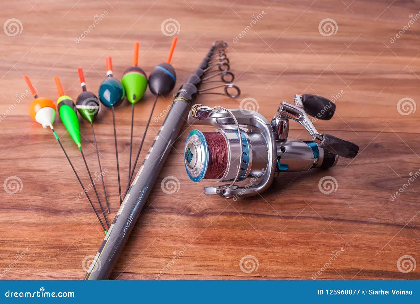 O polo de pesca com anéis e o carretel, flutuadores encontram-se em placas americanas da noz