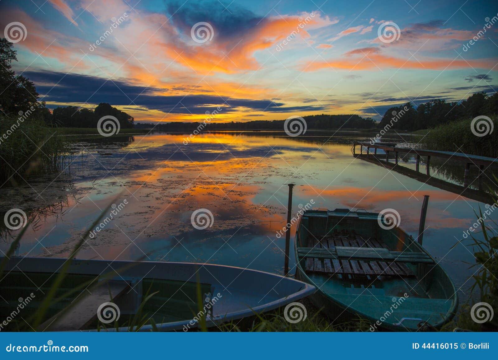 O por do sol alaranjado lindo refletiu na água calma
