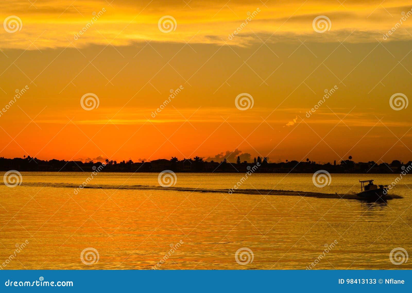 O por do sol com a silhueta de um barco no litoral inter em Belleair blefa, FloridaSunset com a silhueta de um barco no i