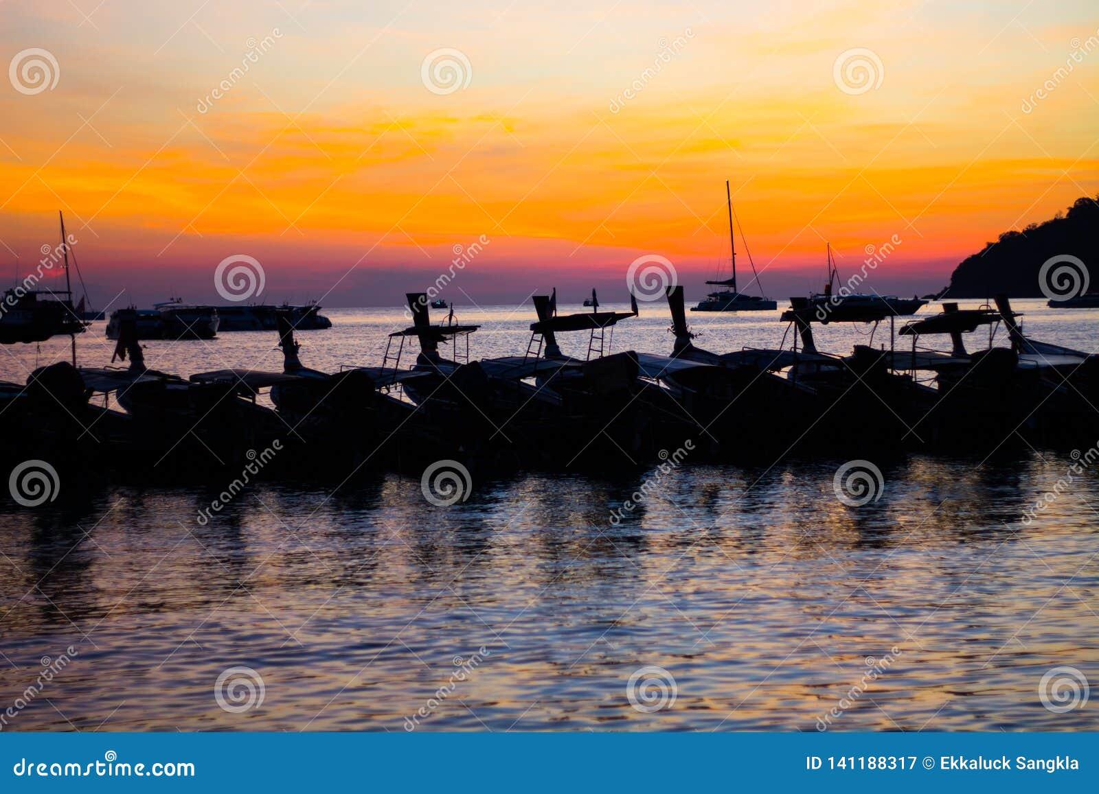 O por do sol na praia e no barco no estilo da silhueta