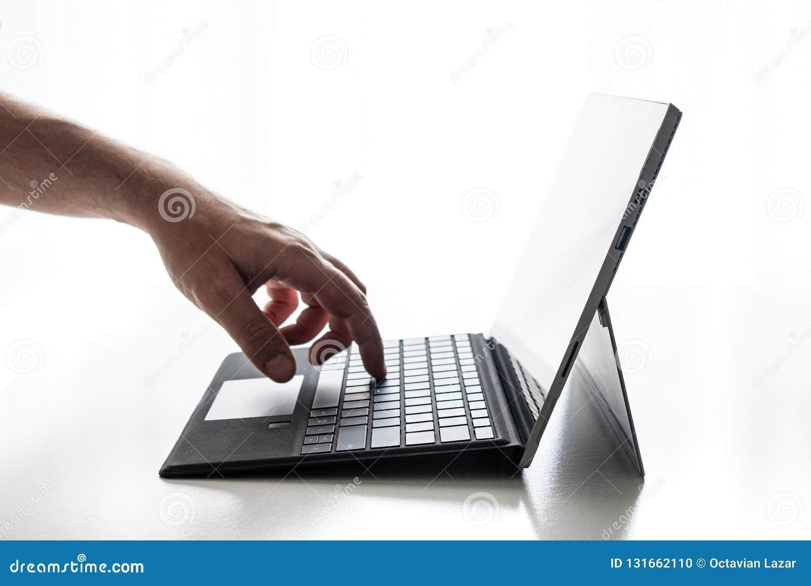 O portátil compacto expôs a mão pura do fundo das chaves e o dedo brancos dos dedos que empurram na chave