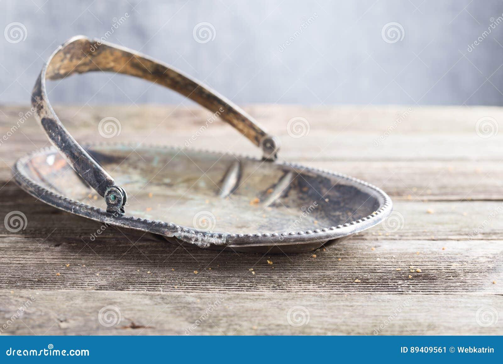 O prato escurecido velho do metal em uma tabela de madeira