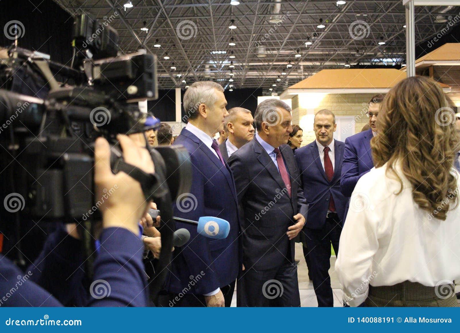 O prefeito, o regulador da cidade de Novosibirsk atendeu à exposição anual da construção Novosibirsk Expocentre o 21 de fevereiro