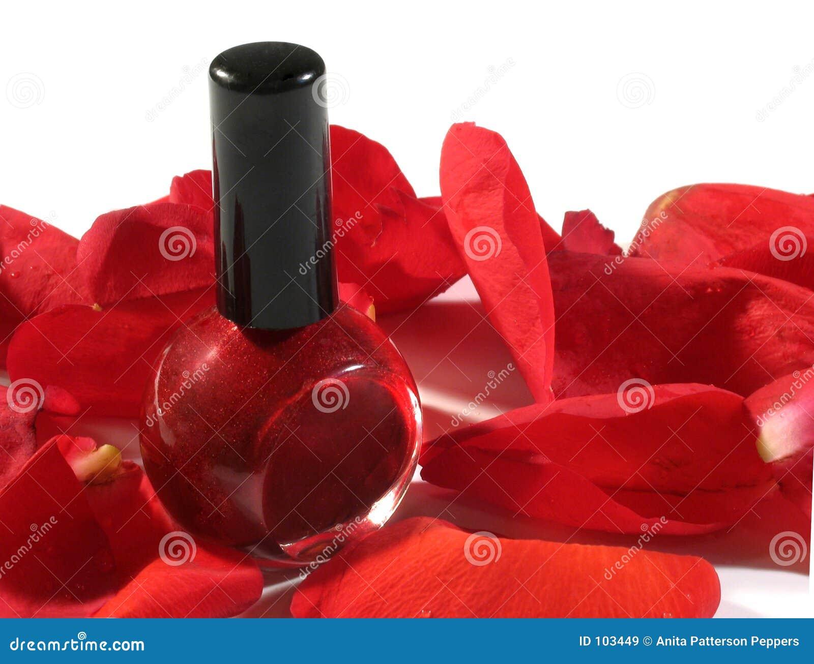 O prego vermelho lustra com pétalas cor-de-rosa