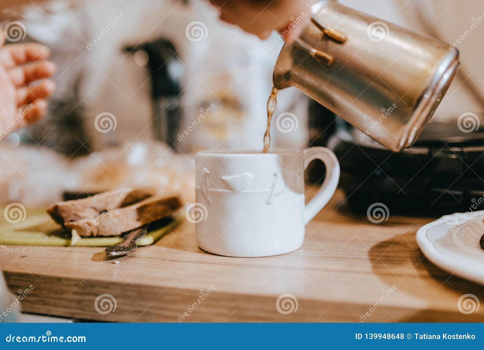 O processo de derramar o café dos turcos em um copo branco bonito na cozinha em uma tabela de madeira