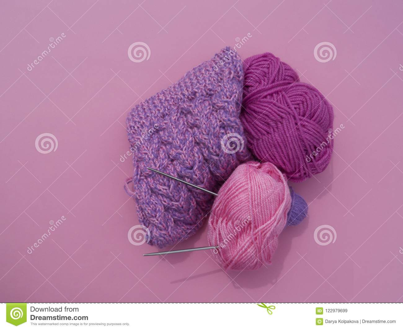 O processo de fazer malha um tampão lilás Linhas de lã em um fundo cor-de-rosa Fio acolhedor