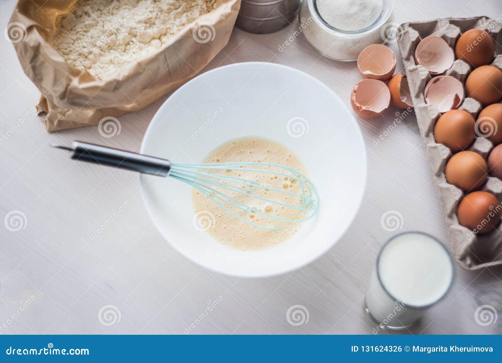 O processo de fazer a massa, a mão da mulher chicoteia ovos e farinha na composição colocada lisa da bacia dos ingredientes e da