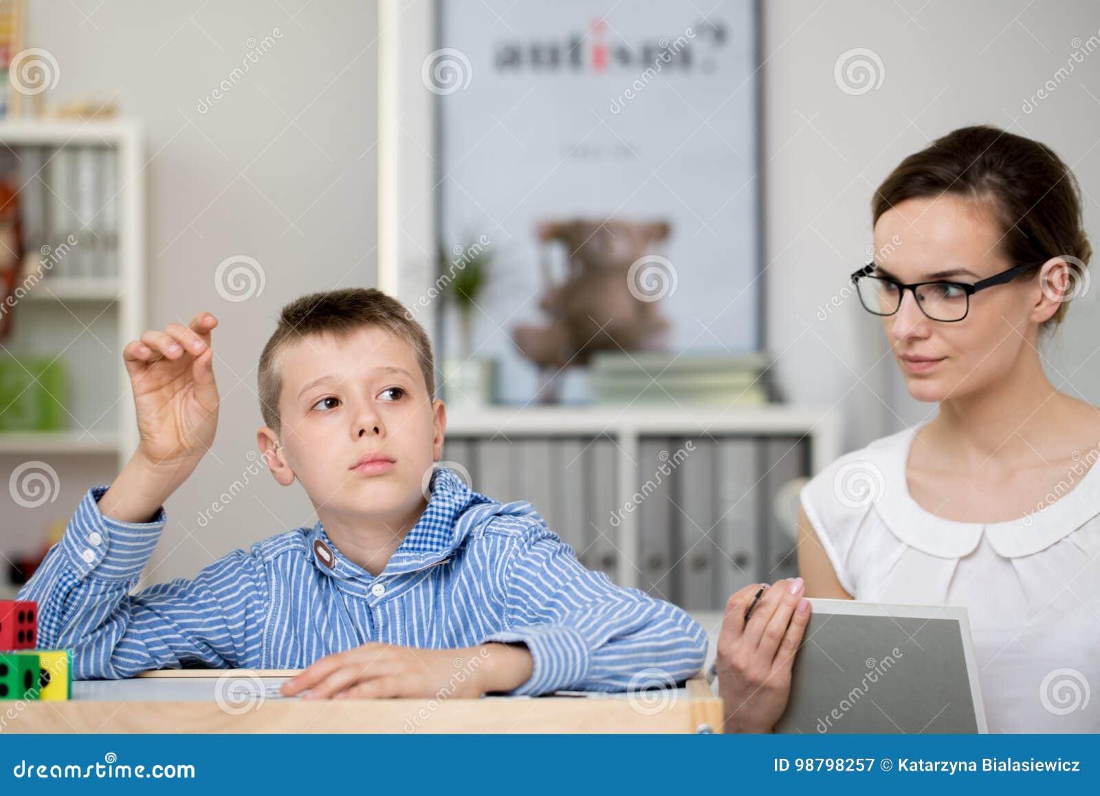 O professor com caderno observa o menino
