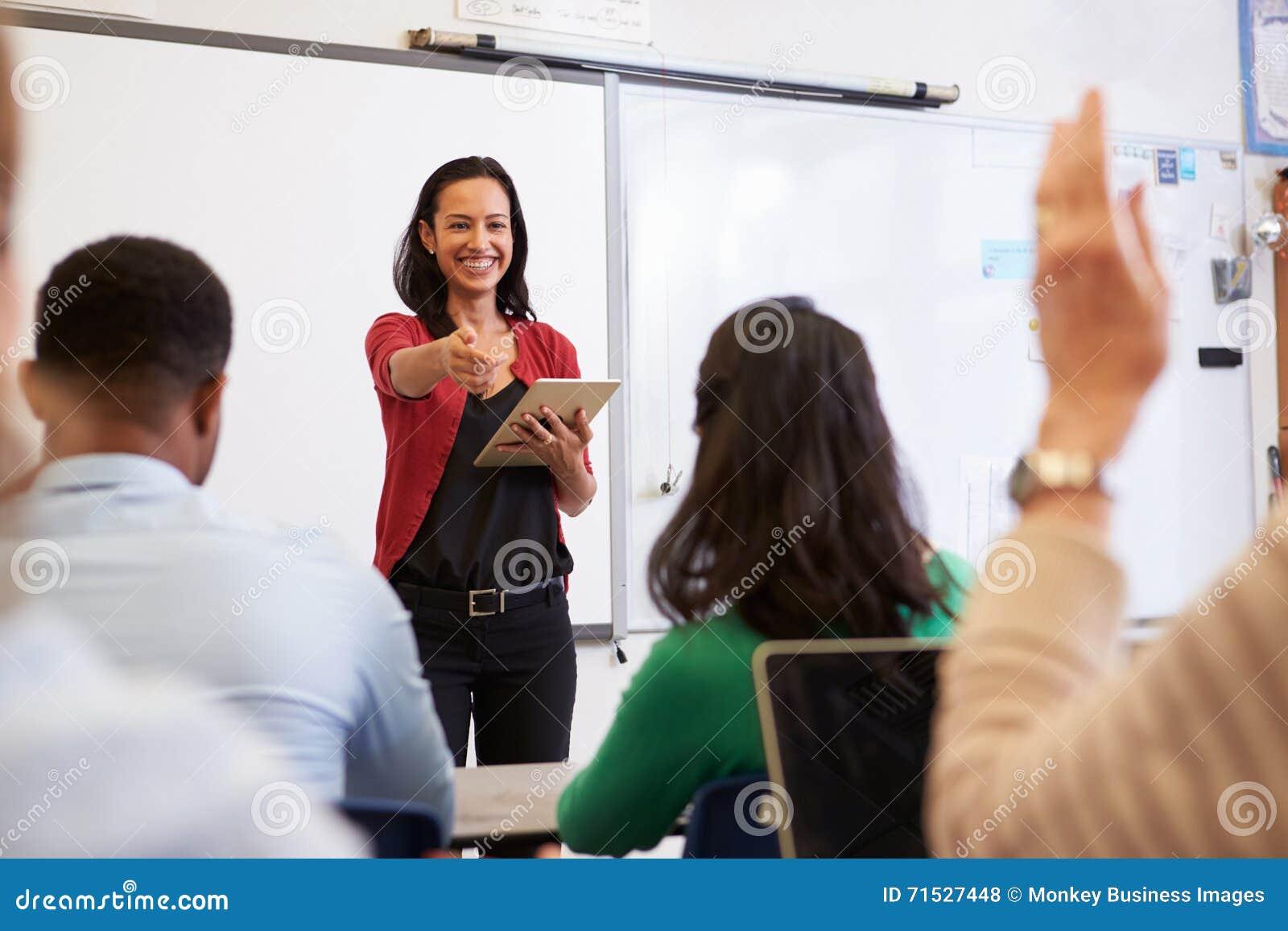 O professor com tabuleta e os estudantes em um ensino para adultos classificam