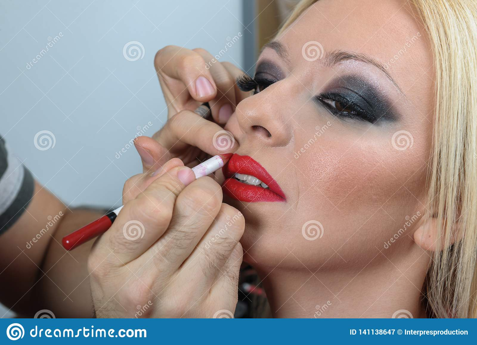O profissional compõe o artista que aplica o batom a uma cara modelo nova