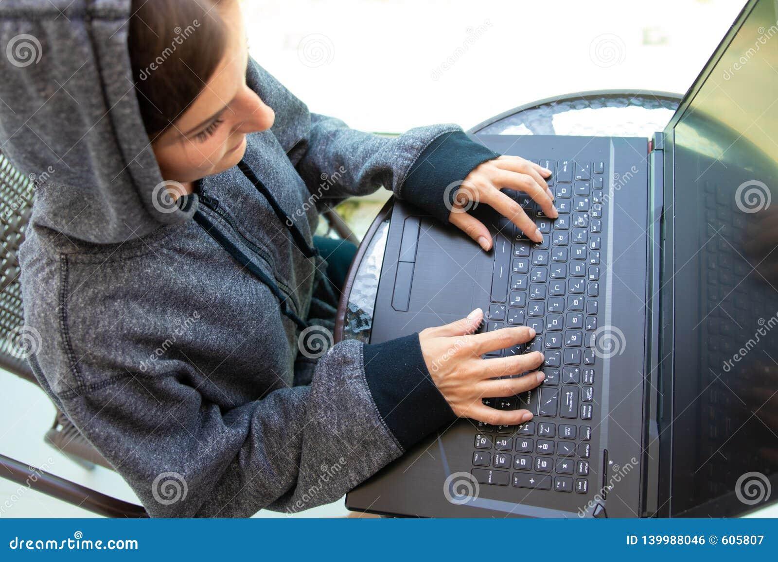 O programador do hacker da mulher está trabalhando no computador no centro da segurança do cyber enchido com as telas de exposiçã