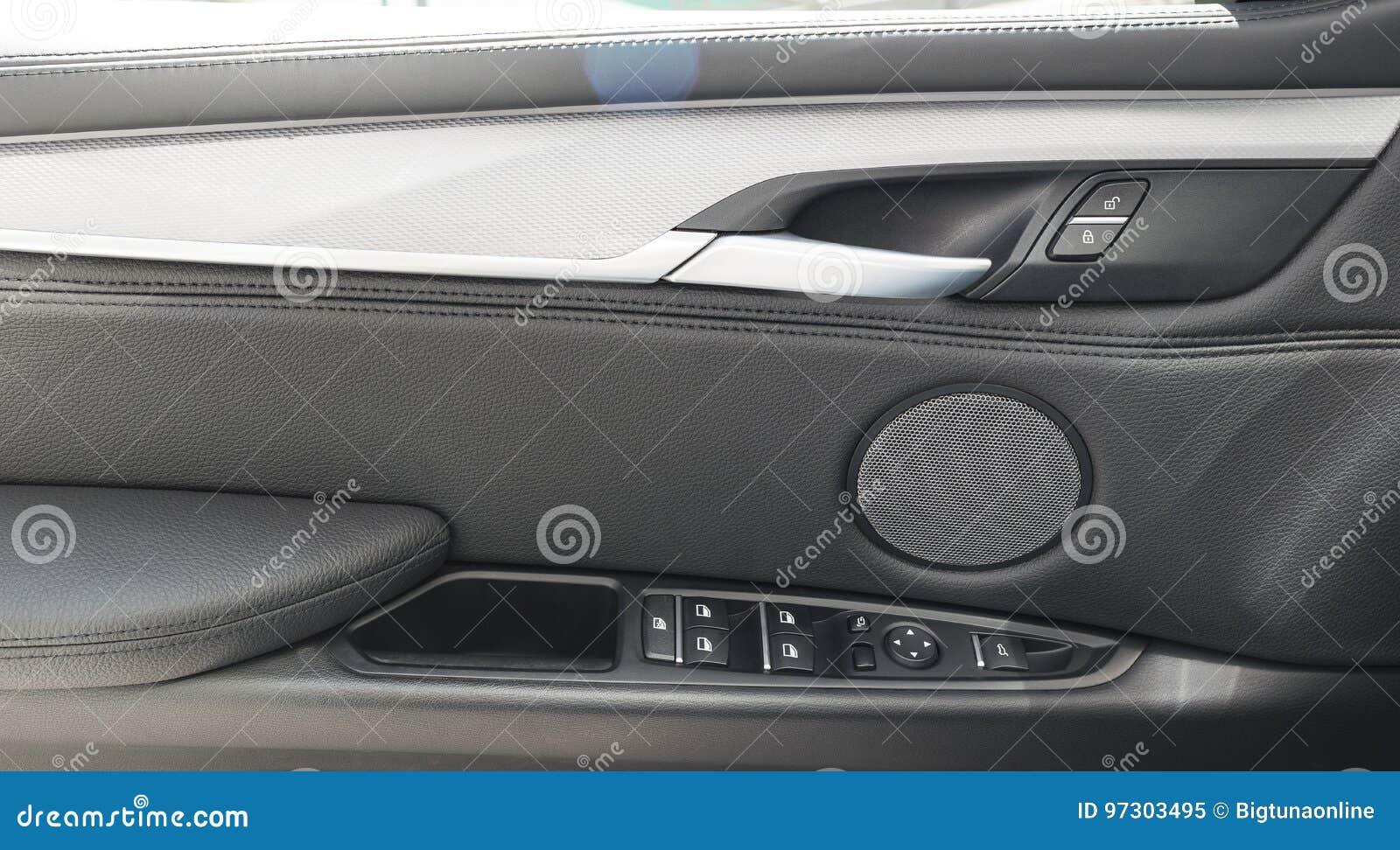 O puxador da porta do carro dentro do carro moderno luxuoso com o botão preto do couro e de interruptor controla detalhes moderno