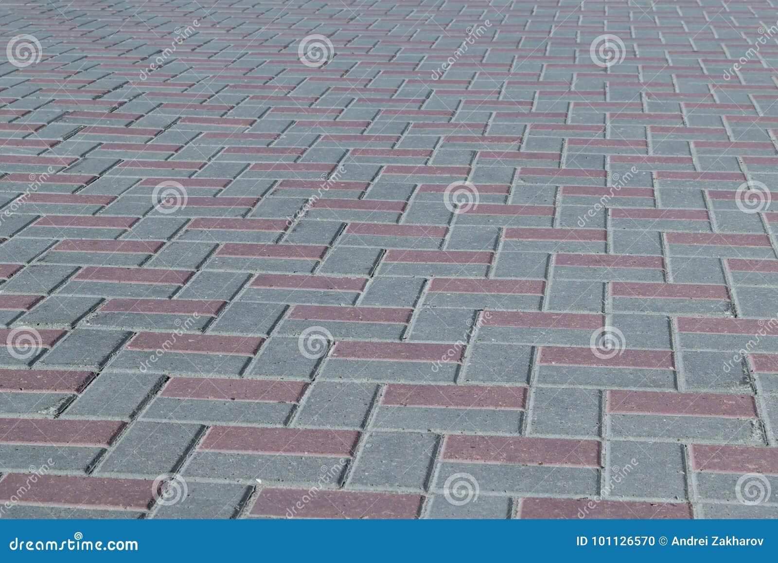 O quadrado ou em um passeio alinhou com as telhas marrons e cinzentas, pedras de pavimentação