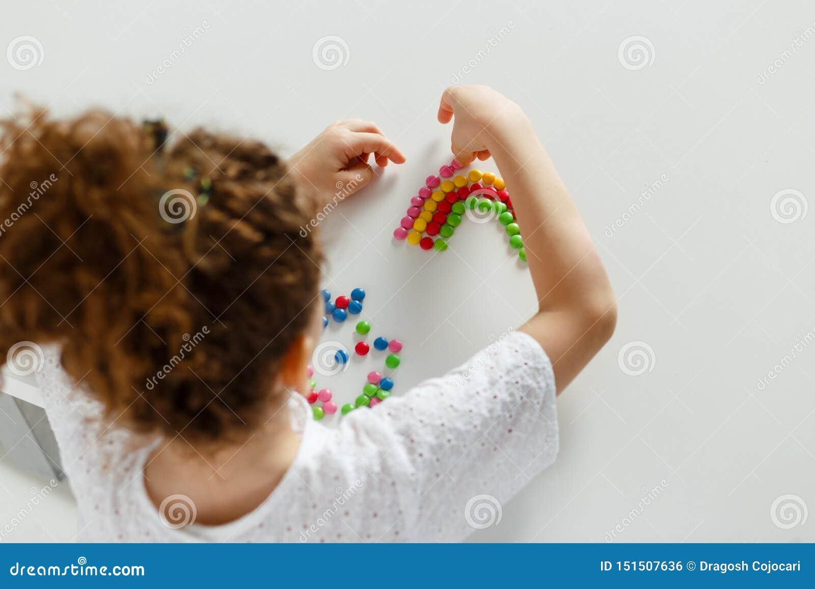 O quadro da imagem de uma menina de cabelo encaracolado arranjou o raidbolw dos doces coloridos, no tabel branco, no estúdio