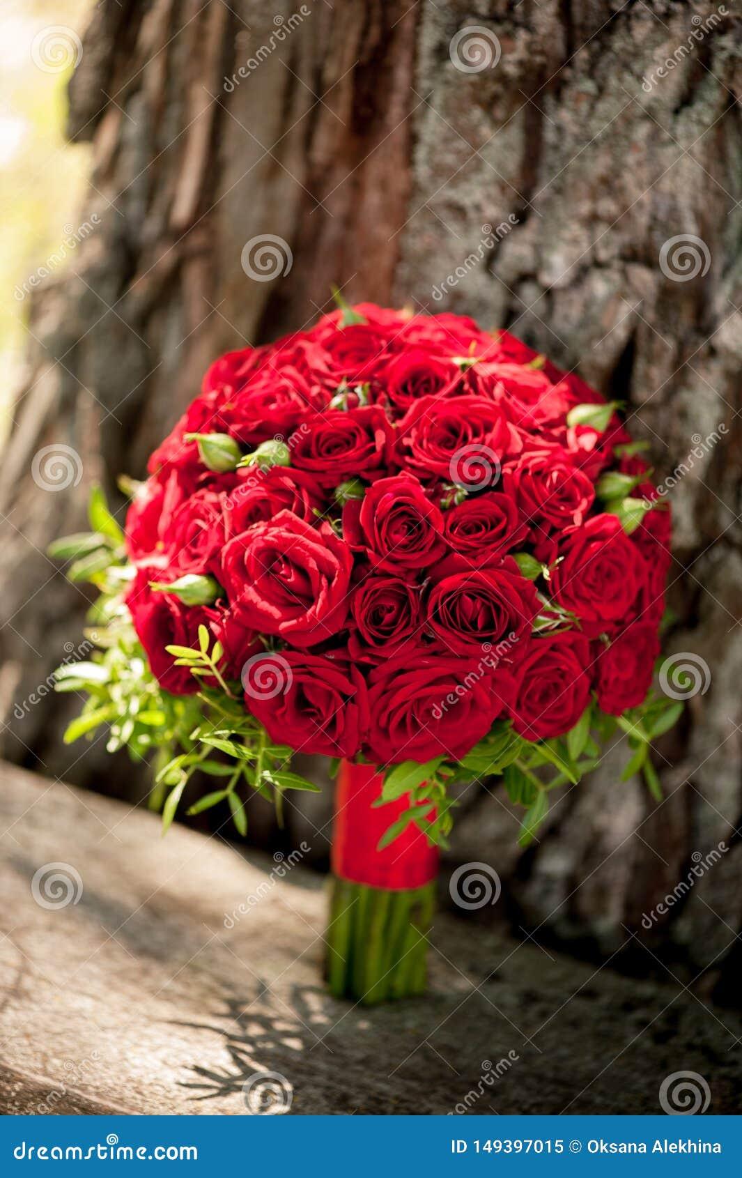 O ramalhete do casamento de rosas vermelhas est? no fundo da casca de ?rvore