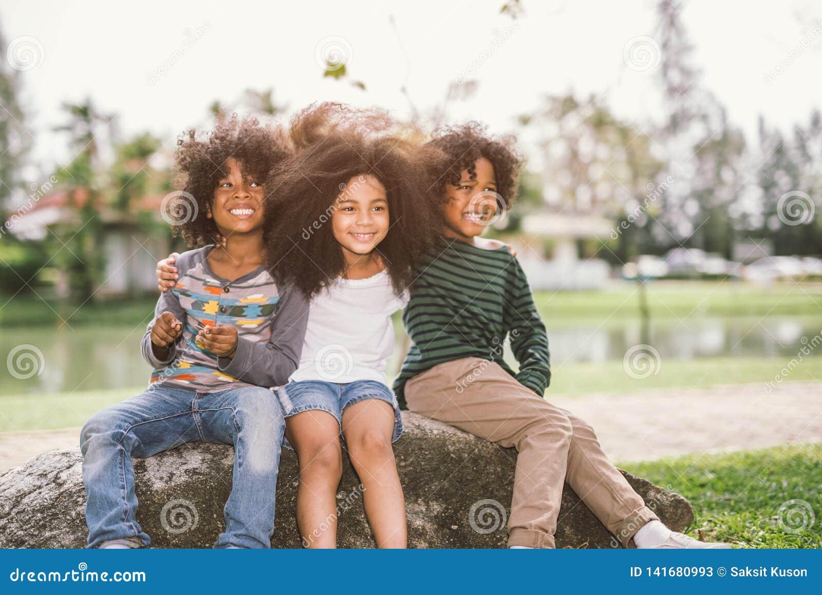 O rapaz pequeno afro-americano bonito e a menina abraçam-se no dia ensolarado do verão