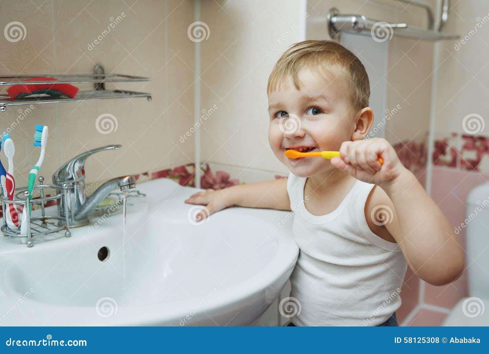 O rapaz pequeno aprende escovar os dentes