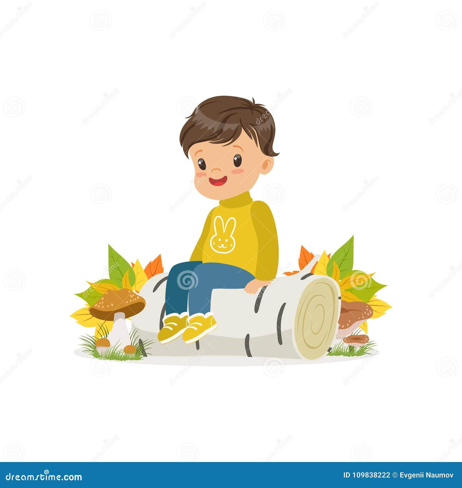 O rapaz pequeno bonito na roupa morna que senta-se na floresta do outono do início de uma sessão do vidoeiro, criança bonita que