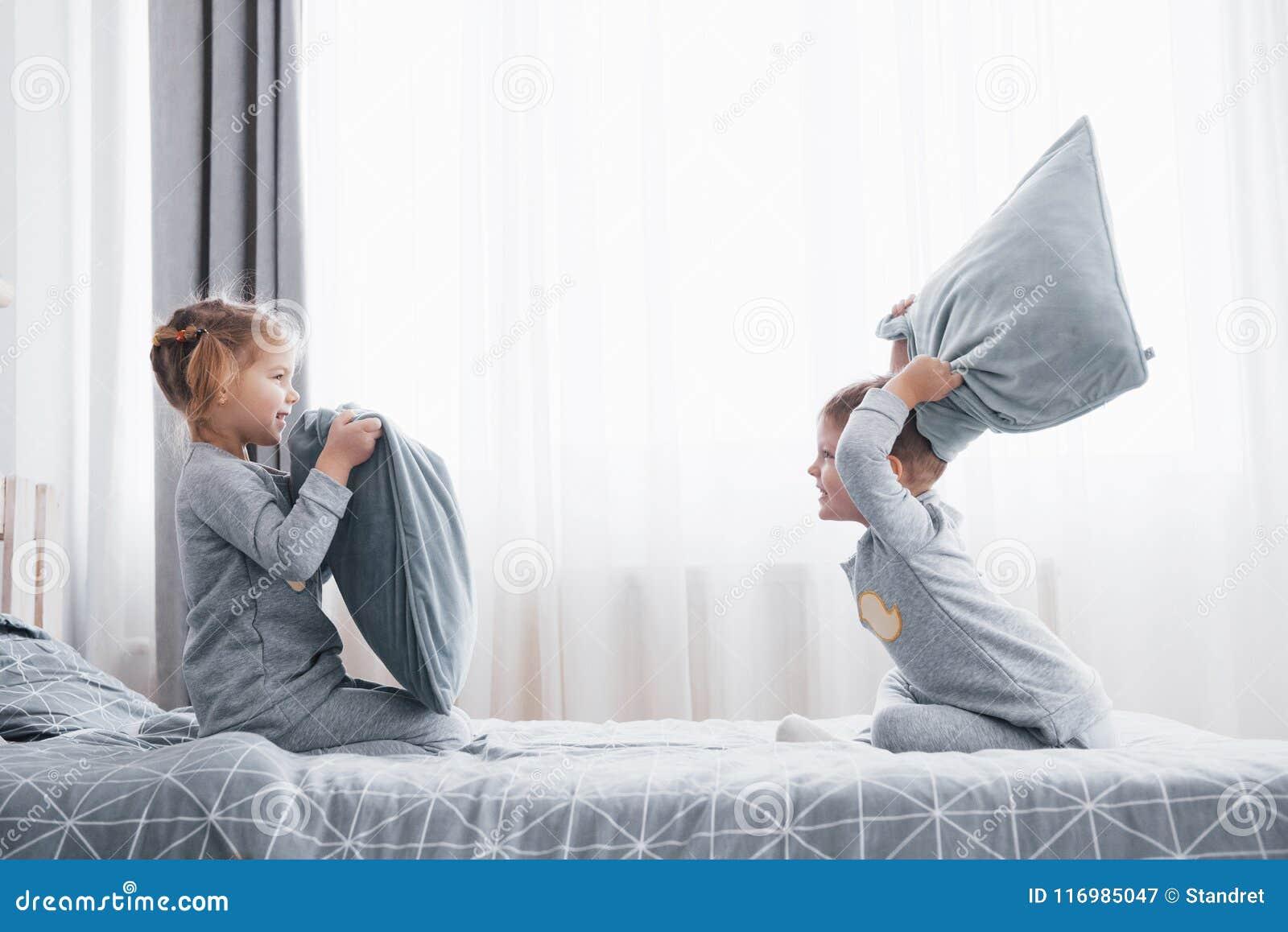 O rapaz pequeno e a menina encenaram uma luta de descanso na cama no quarto Batida impertinente das crianças descansos Gostam