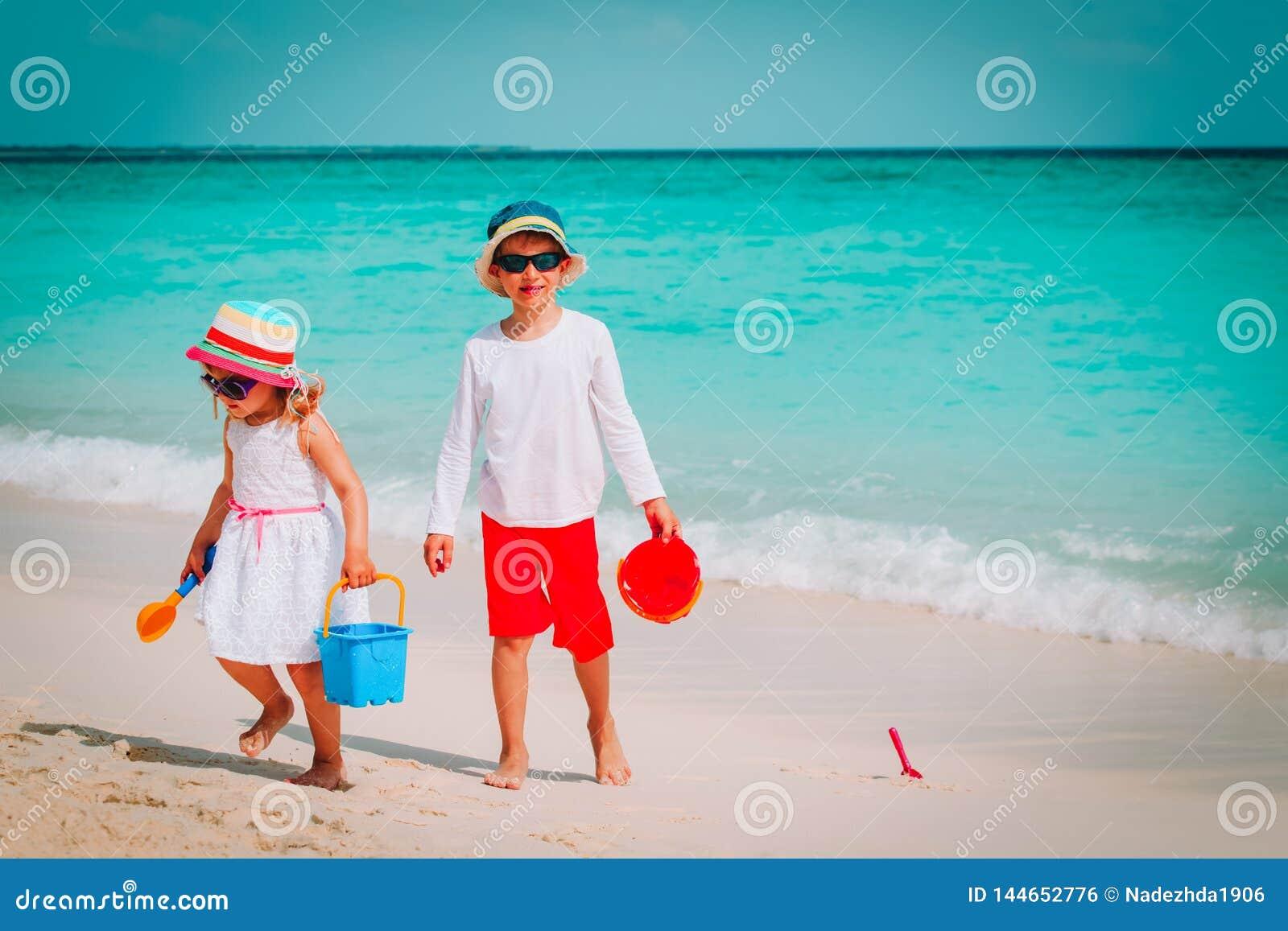 O rapaz pequeno e a menina felizes jogam com a areia na praia