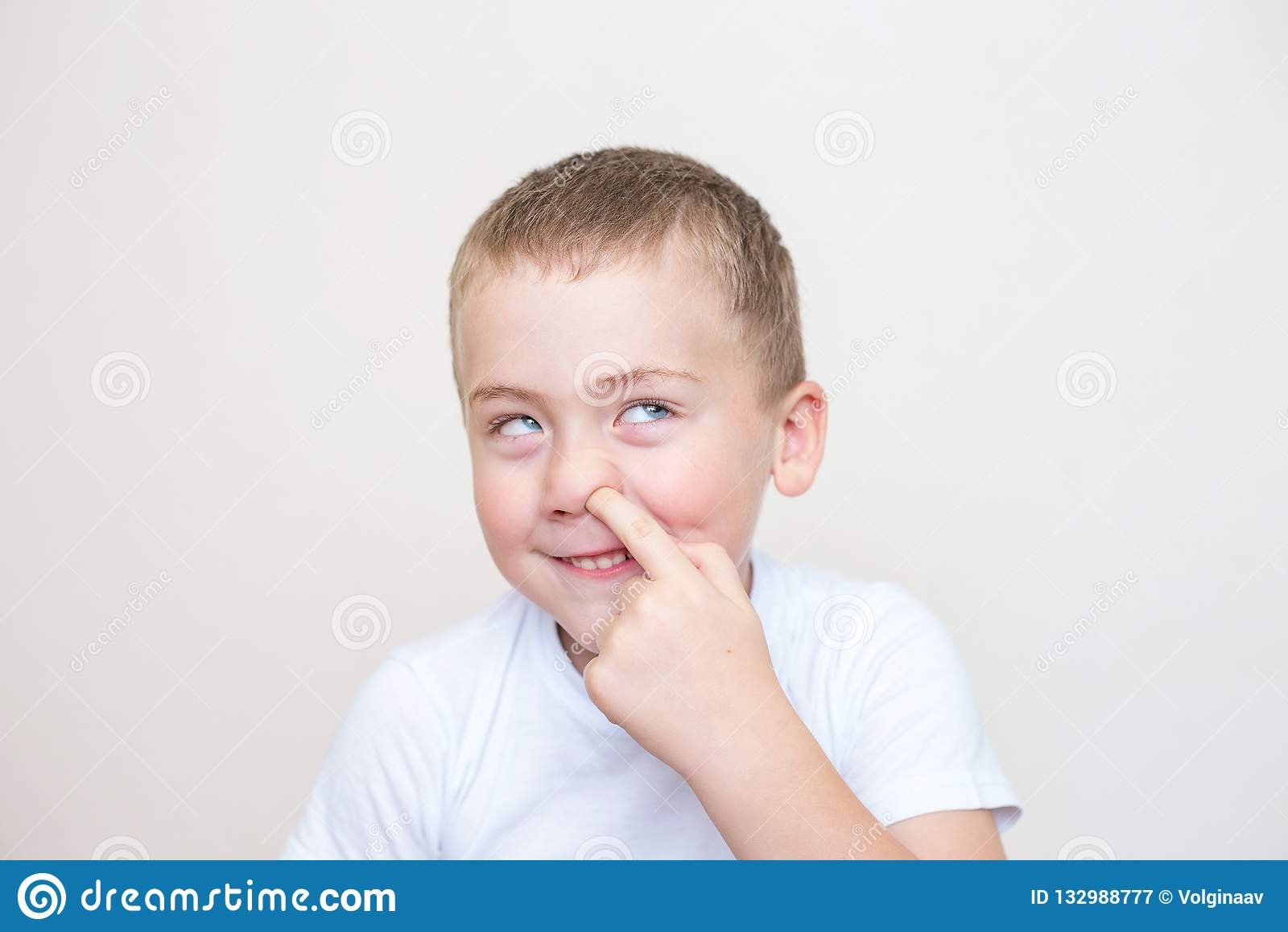O rapaz pequeno está escolhendo seu nariz em um fundo branco