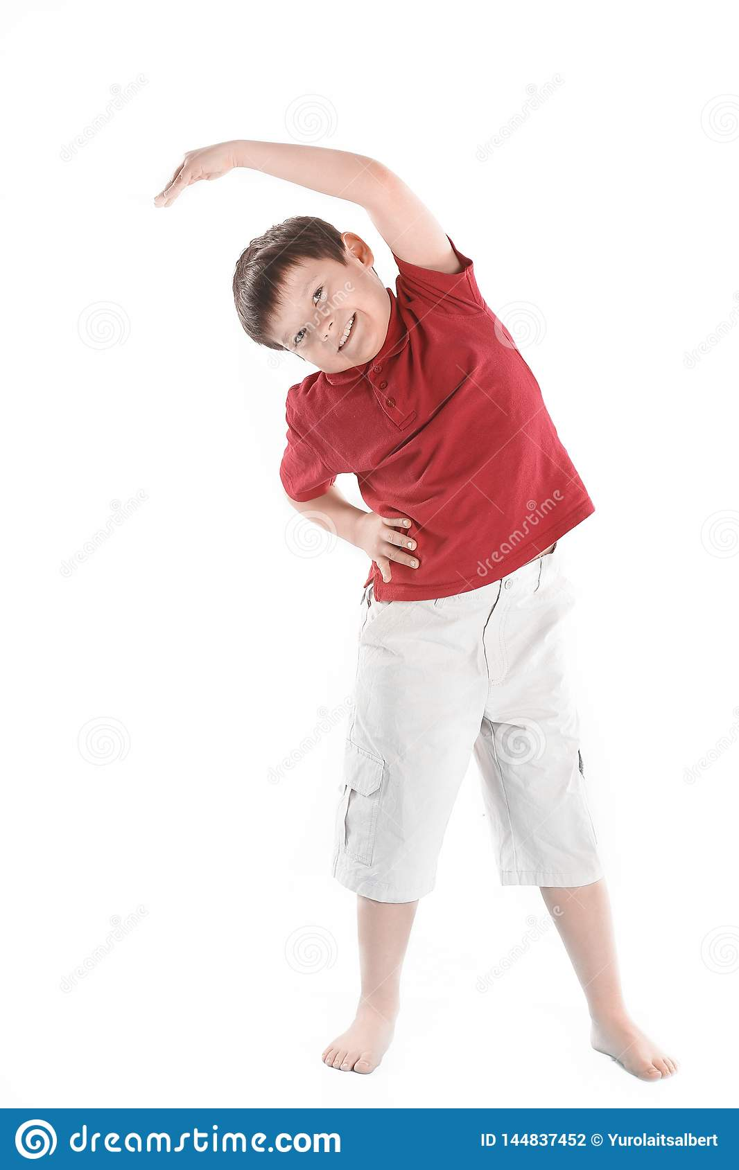 O rapaz pequeno executa um exerc?cio para esticar os m?sculos Isolado no branco
