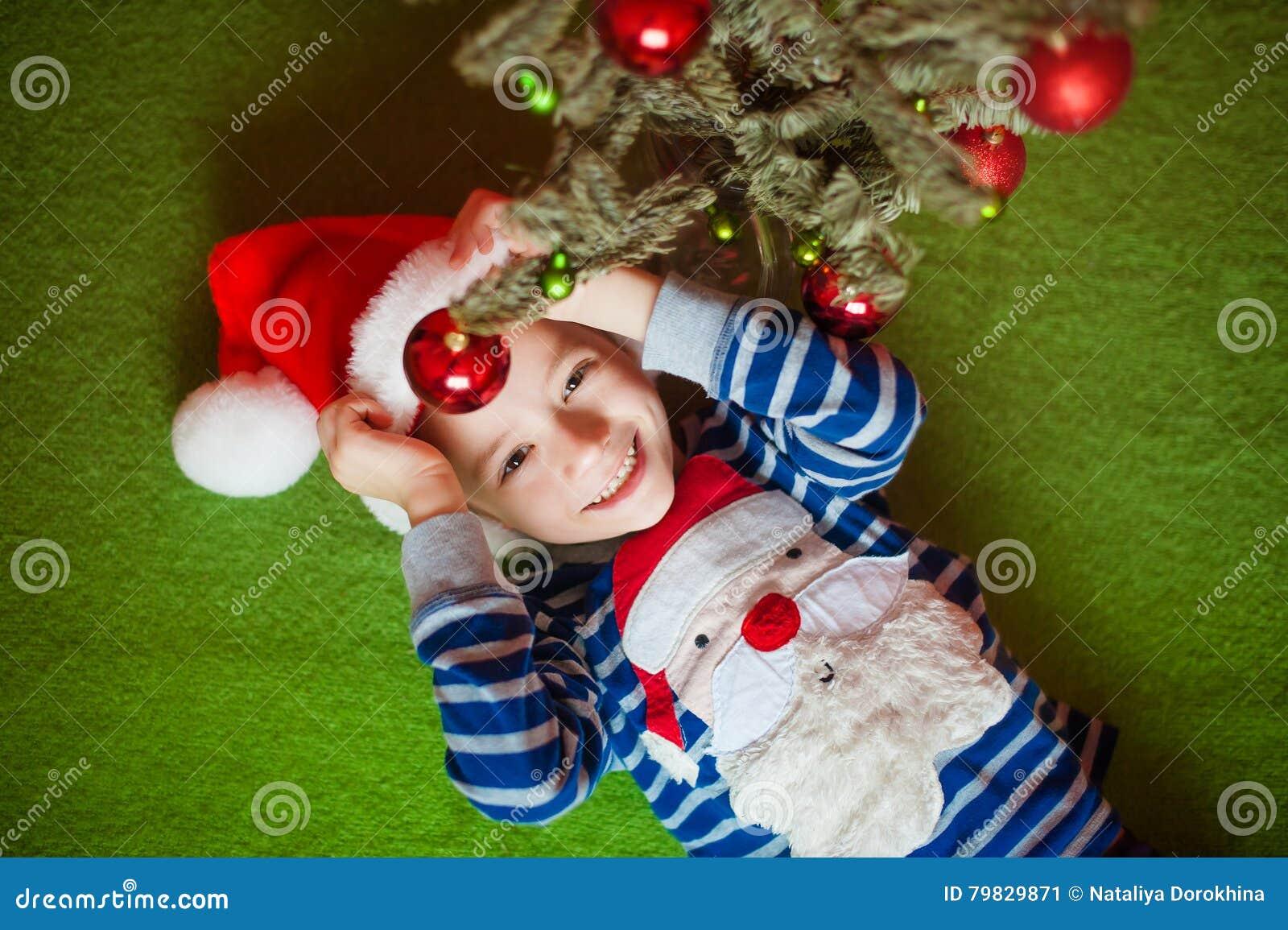 O rapaz pequeno feliz é mentiras perto do abeto Year& novo x27; feriados de s em um t-shirt listrado com Santa Claus