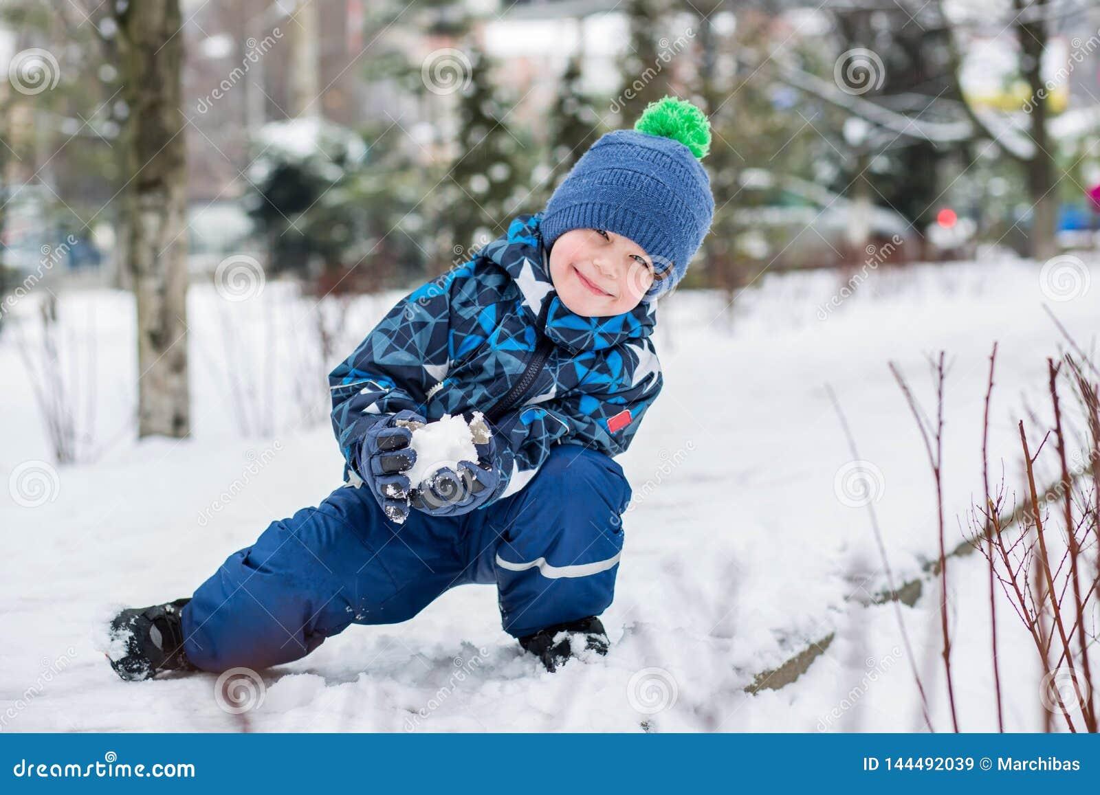 O rapaz pequeno feliz esculpe bolas de neve